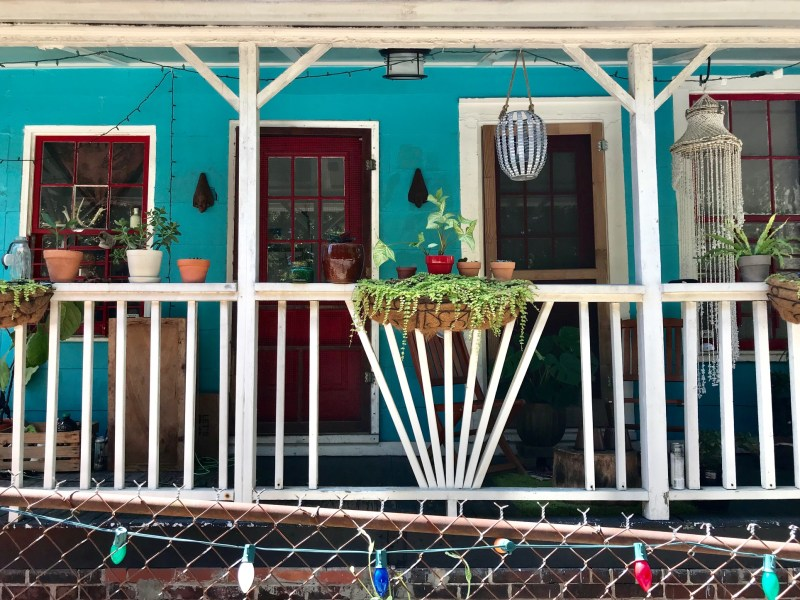 A green house with white railing on the front porch